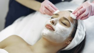 crop woman in medical gloves removing cosmetic mask from face of female client in spa salon